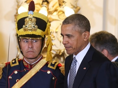 An honor guard looks at US President Barack Obama as he enters the government house in Buenos Aires, Argentina, on Wednesday. AP