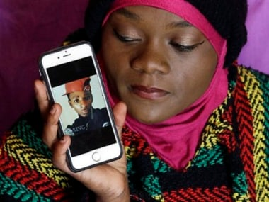 Abdi Mohamed's cousin Muslima Weledi holds a photograph of him during a interview. AP
