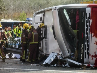 Emergency services personnel stand at the scene of a bus accident crashed on the AP7 highway that links Spain with France on Sunday. AP