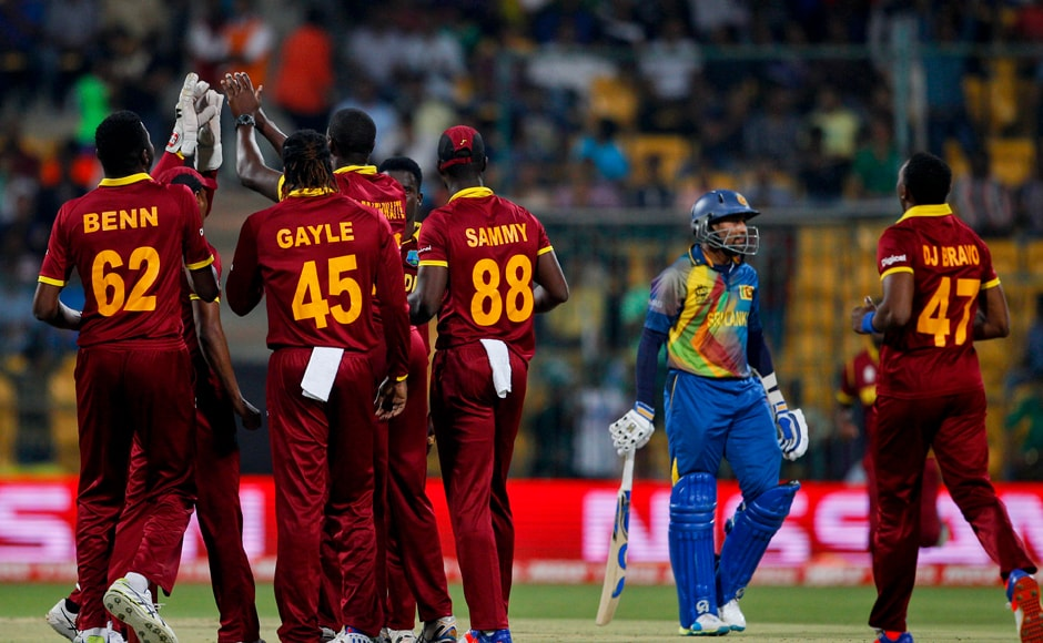 West Indies' players celebrate the dismissal of Sri Lanka's Tillakaratne Dilshan, second right, during their ICC World Twenty20 2016 cricket match in Bangalore, India, Sunday, March 20, 2016. (AP Photo/Aijaz Rahi)