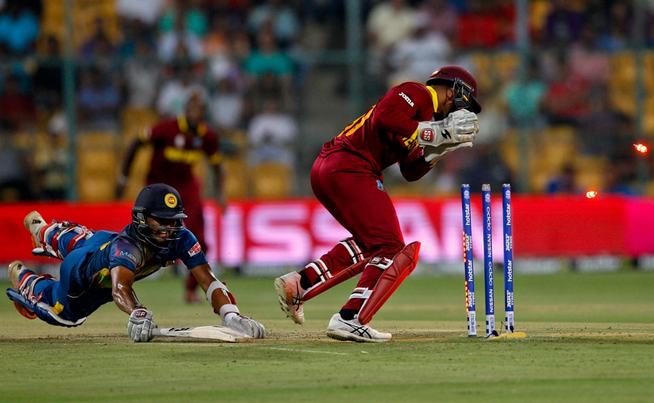 West Indies' wicketkeeper Denesh Ramdin, right, breaks the stumps to run-out Sri Lanka's Dinesh Chandimal, left, during their ICC World Twenty20 2016 cricket match in Bangalore, India, Sunday, March 20, 2016. (AP Photo/Aijaz Rahi)
