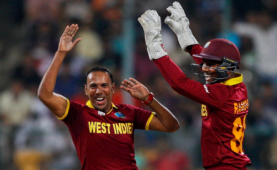 West Indies' Samuel Badree, left, celebrates with teammate Denesh Ramdin the dismissal of Sri Lanka's Milinda Siriwardana during their ICC World Twenty20 2016 cricket match in Bangalore, India, Sunday, March 20, 2016. (AP Photo/Aijaz Rahi)