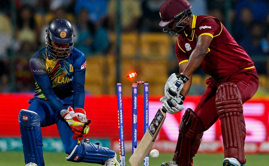 West Indies' Johnson Charles, right, is bowled out by Sri Lanka's Jeffrey Vandersay during their ICC World Twenty20 2016 cricket match in Bangalore, India, Sunday, March 20, 2016. (AP Photo/Aijaz Rahi)