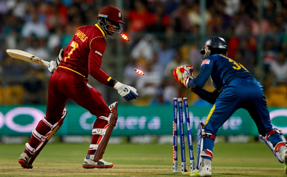 Sri Lanka's wicketkeeper Dinesh Chandimal, right, stumps out West Indies' Marlon Samuels, left, during their ICC World Twenty20 2016 cricket match in Bangalore, India, Sunday, March 20, 2016. (AP Photo/Aijaz Rahi)