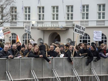 """Demonstrators hold posters reading """"Have you no shame"""" during a protest gather outside the parliament in Reykjavik. AFP"""