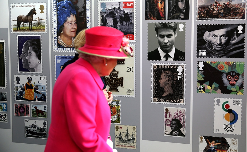 Queen Elizabeth II looks at commemorative postal stamps. Reuters