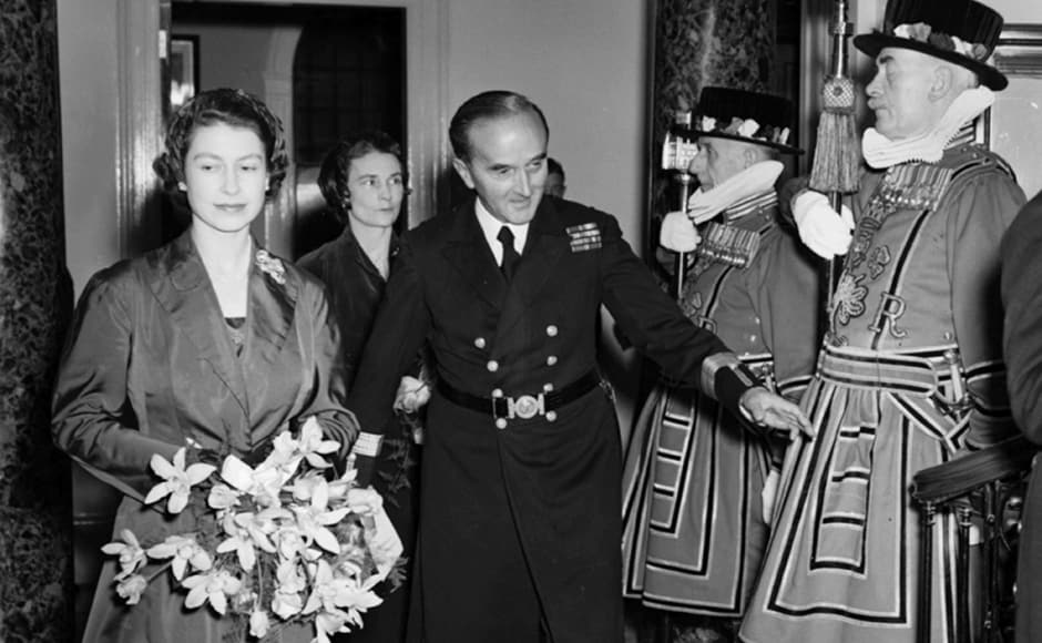 Queen Elizabeth II holding a bouquet of flowers as Captain G Curteis, Deputy Master of Trinity House, introduces her to the Yeoman of the Guard as they tour the rebuilt Trinity House on Tower Hill, 21 October 1953. Reg Speller/Fox Photos/Getty Images
