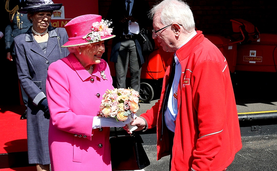 Queen Elizabeth II meets Britain's longest serving postman Bob Hartley. Reuters