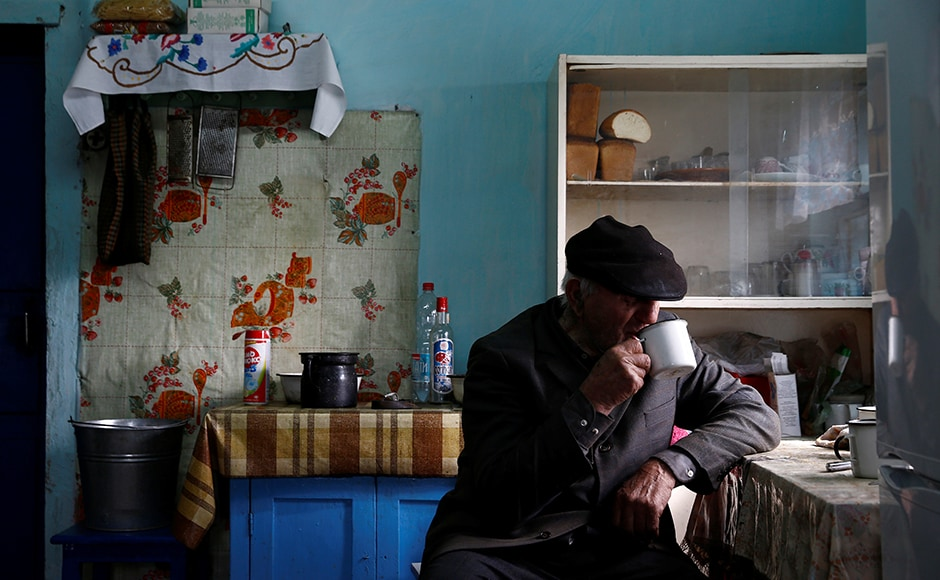 Ivan Shamyanok, 90, drinks tea in his house in the village of Tulgovichi, near the exclusion zone around the Chernobyl nuclear reactor, Belarus .Shamyanok says the secret to a long life is not leaving your birthplace even when it is a Belarusian village poisoned with radioactive fallout from a nuclear disaster. Shamyanok and his nephew are the only ones living in the village. Image courtesy: Reuters