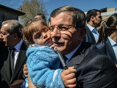 Turkish Prime Minister Ahmet Davutoglu (R) holds a child during a visit to Diyarbakir. AFP