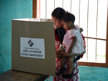 A voter holds a child as she casts her ballot in the state assembly elections at a polling station in Diphu in the Karbi Anglong district some 215kms from Guwahati. AFP