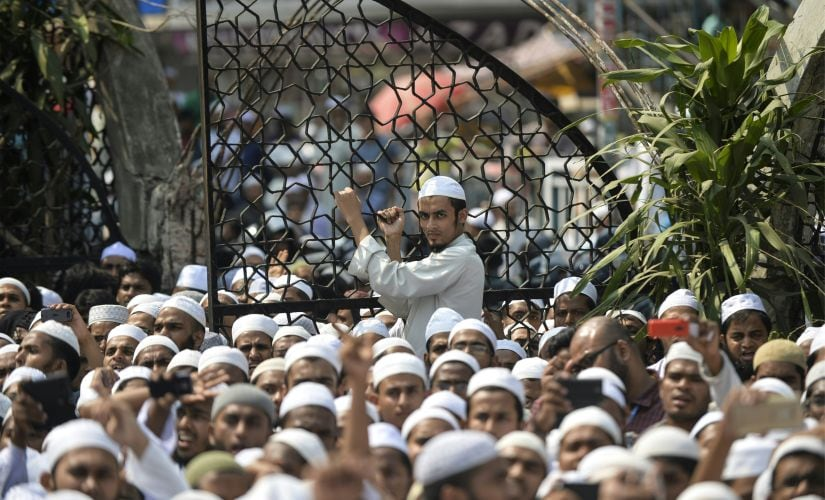 """Bangladeshi hardline Islamists protest outside the national mosque Baitul Mukarram in Dhaka on March 25, 2016. Thousands of Bangladeshi hardline Islamists have rallied across the country against an """"infidels'-initiated"""" move to scrap Islam as the state-religion in the Muslim-majority nation. Nearly seven thousand activists of hardline group Hefazat-e-Islam carried banners and festoons and chanted slogans on Dhaka high roads after the Friday prayer booing the government for not taking """"sufficient actions"""" to stop """"mockery"""" against Islam, religion of nearly 90 percent of the population of the country. / AFP PHOTO / MUNIR UZ ZAMAN"""