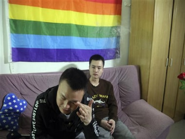In this photo taken Tuesday, Sun Wenlin, right, sits with his partner Hu Mingliang at home a day before going to court to argue in China's first gay marriage case in Changsha in central China's Hunan province. AP