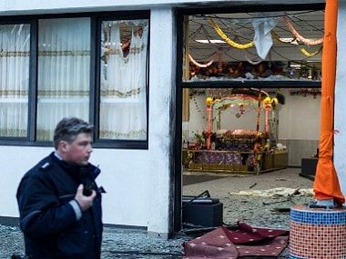 A police officer passes by the gurudwara after three people have been injured in an apparently deliberate explosion Saturday evening, in the western German city of Essen. Marcel Kusch/dpa via AP