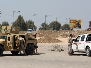Iraqi security forces check vehicles at the site of a suicide attack targeting a joint police and army checkpoint, near Muthana Brdige in northern Baghdad. AFP