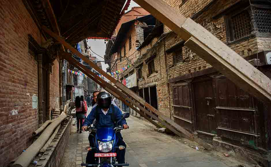 A biker navigates through an alley blocked by wooden pillars supporting the damaged walls of the Durbar square. Image courtesy: Smita Sharma