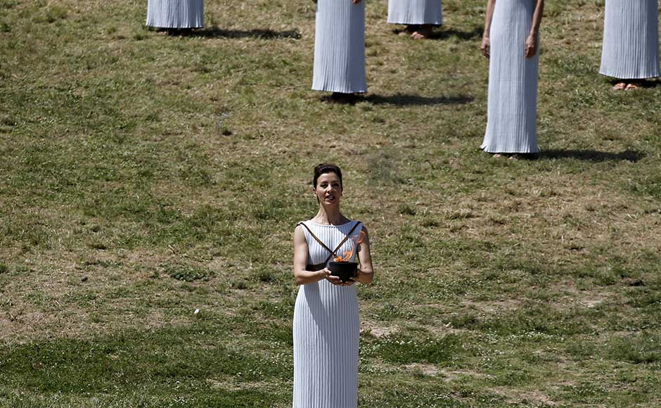Katerina Lehou, playing the role of High Priestess, carries the Olympic flame during the dress rehearsal. REUTERS/Alkis Konstantinidis