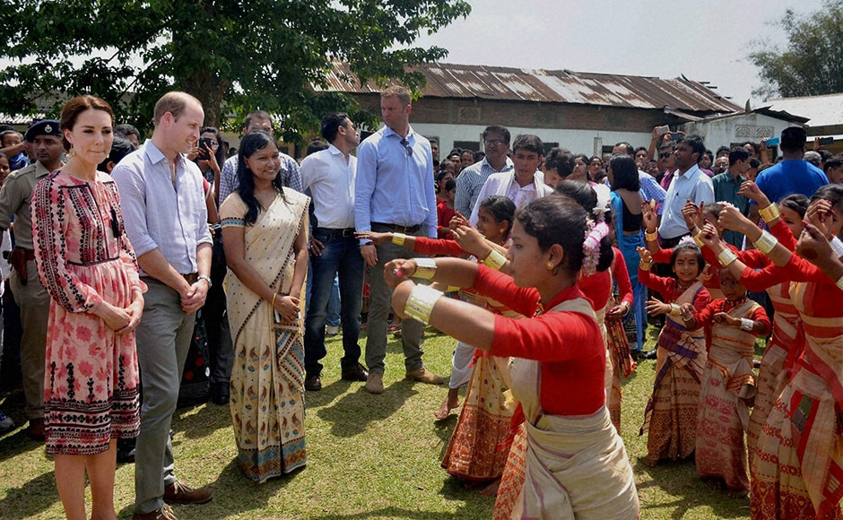 Prince William and Kate are welcomed by village women during their visit to Panbari Model village near Kaziranga. PTI Photo