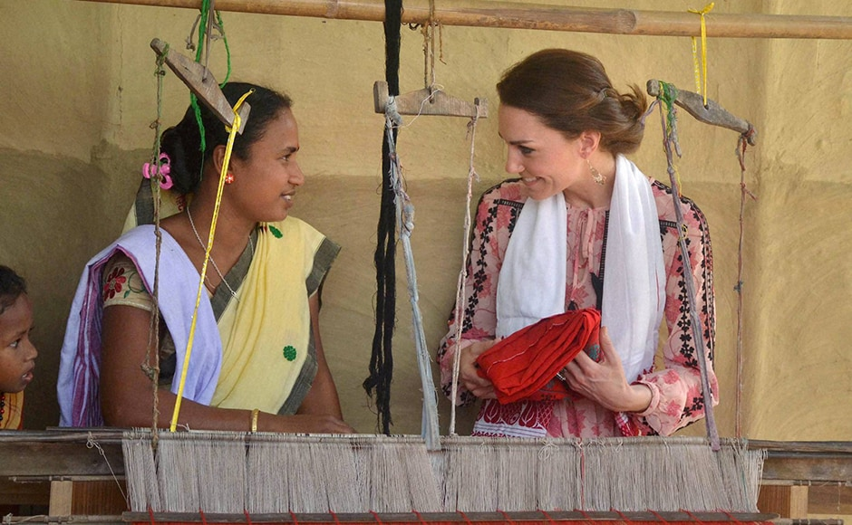 Kate receives a traditional cloth as a gift from a weaver during a visit to Panbari Model village near Kaziranga, Assam on Wednesday. PTI Photo