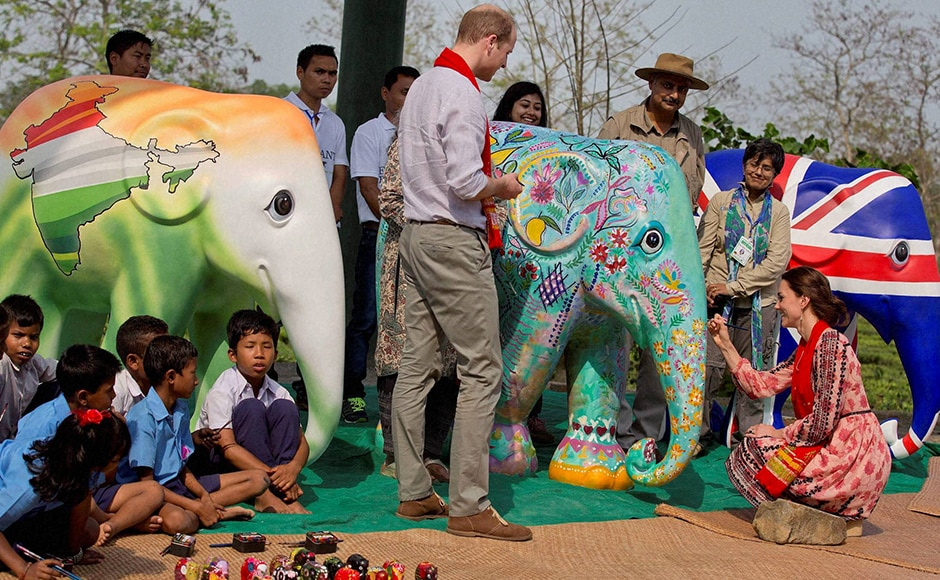 Kate gives a finishing touch of paint to a statue as Prince William looks on, at the CWRC at Panbari reserve forest. PTI Photo