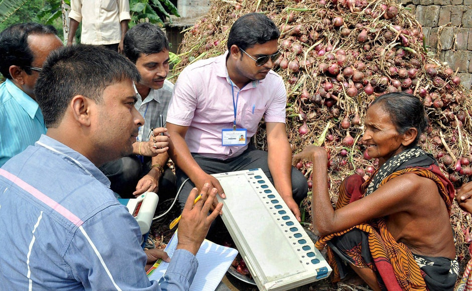 Election Commission officials demonstrate the working of the Election Voting Machine (EVM) to an elderly women farmer during a voting awareness programme for upcoming assembly elections in Murshidabad district on Monday. PTI