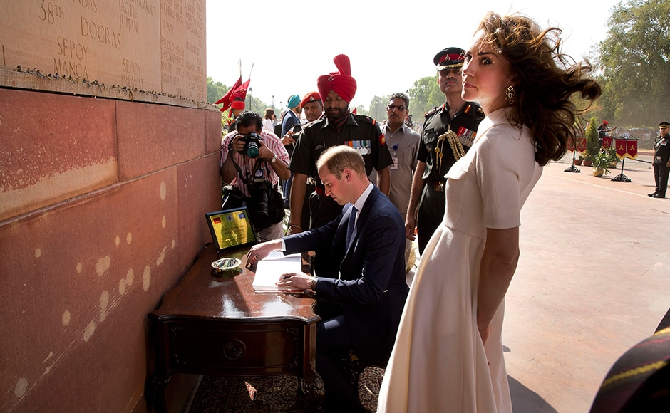 Prince William signs the visitor's book as his wife Katelooks on at the India Gate war memorial in New Delhi. AFP