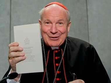 Cardinal Christoph Schoenborn shows a copy of ' Amoris Laetitia ' (The Joy of Love) during a press conference at the Vatican. AP