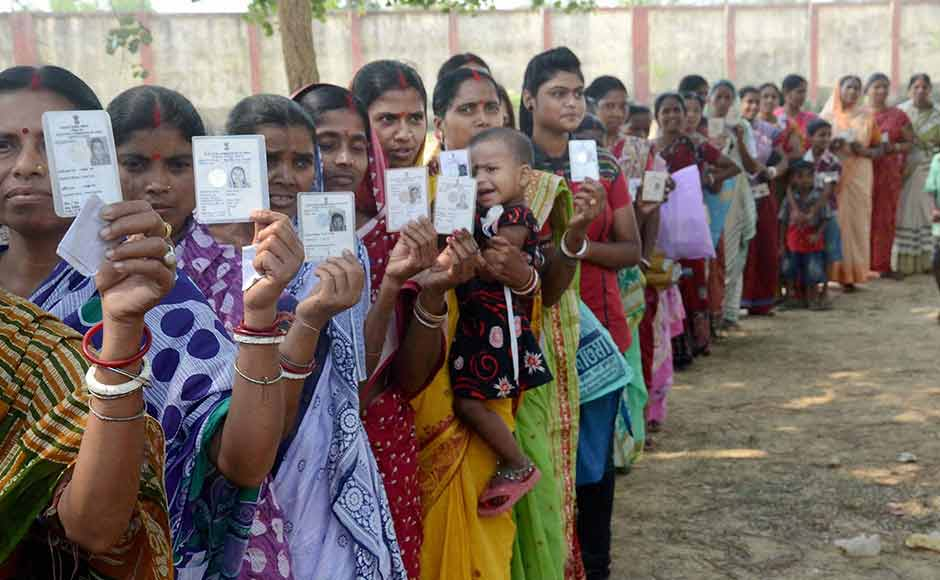 Voters wait in a queue to cast votes at a polling station during the state assembly elections in Kharagpur, West Bengal on Monday. PTI