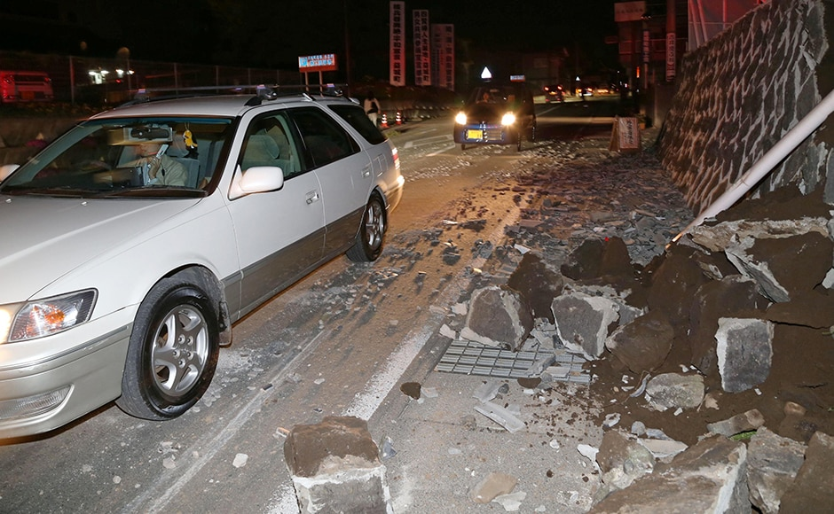 Cars move past fallen walls after the earthquake in Mashiki. The epicenter was 120 kilometers (74 mile) northeast of the Sendai nuclear plant, the only one operating in the country. AP