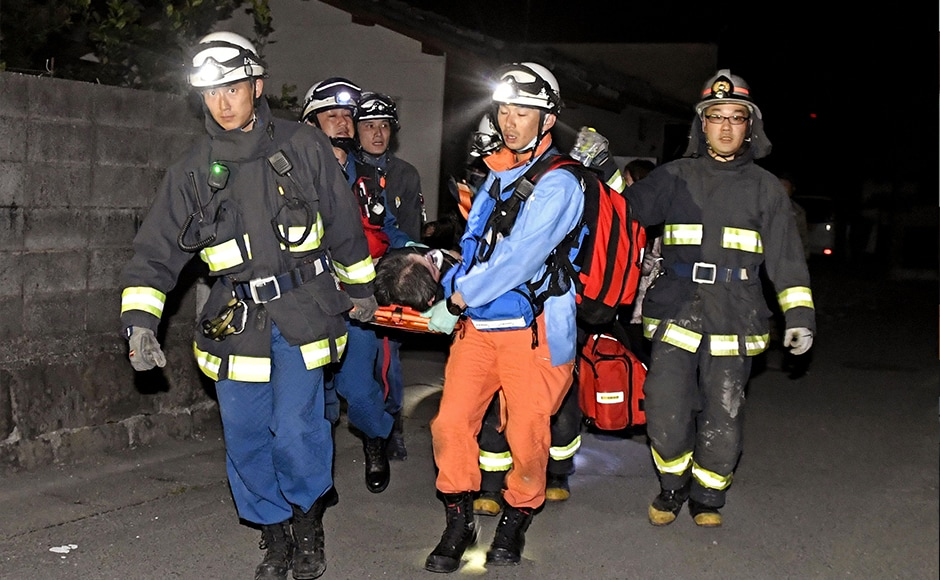 Firefighters carry an injured person after the earthquake in Mashiki, southern Japan. The country's Chief Cabinet Secretary Yoshihide Suga told a news conference that damage was being assessed, but there were no abnormalities at nearby nuclear facilities. AP