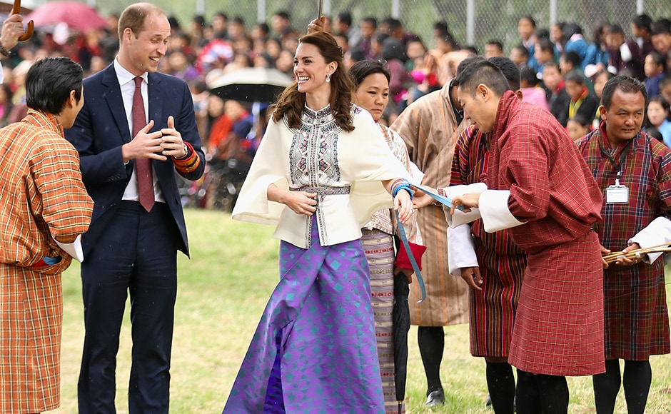 Prince William, Duke of Cambridge looks on as Catherine, Duchess of Cambridge fires an arrow during an Bhutanese archery demonstration on the first day of a two day visit to Bhutan. Getty