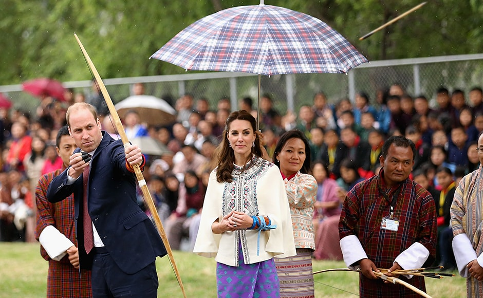 Prince William, Duke of Cambridge fires an arrow as Catherine, Duchess of Cambridge looks on during an Bhutanese archery demonstration on the first day of a two day visit to Bhutan. Getty