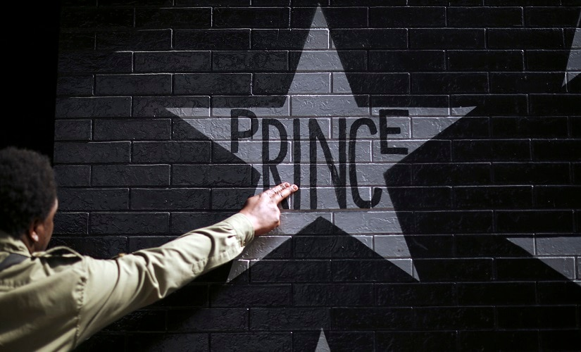 A fan touches Prince's star on the wall of First Avenue on Thursday. AP