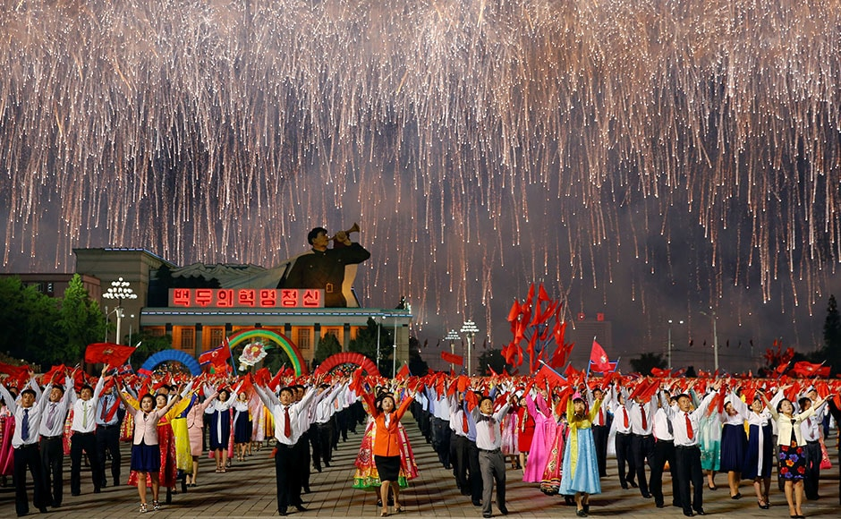Fireworks explode over participants in a mass dance in the capital's main ceremonial square, a day after the ruling Workers' Party of Korea party wrapped up its first congress in 36 years, in Pyongyang. Reuters