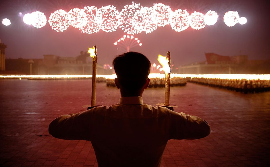 Fireworks explode over participants carrying torches during a torchlight procession in the capital's main ceremonial square, a day after the ruling Workers' Party of Korea party wrapped up its first congress in 36 years, in Pyongyang, North Korea. Reuters