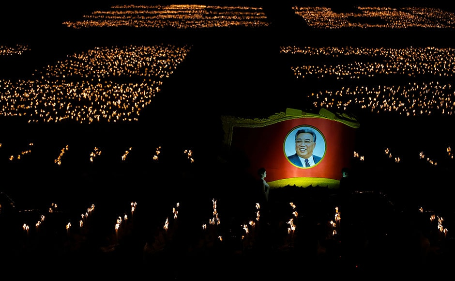 Participants carry torches and a picture of former North Korean leader Kim Il Sung during a torchlight procession in the capital's main ceremonial square. Reuters