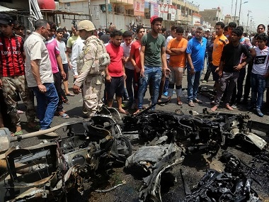 Security forces and citizens inspect the scene after a car bomb explosion at a crowded outdoor market in Baghdad. AP