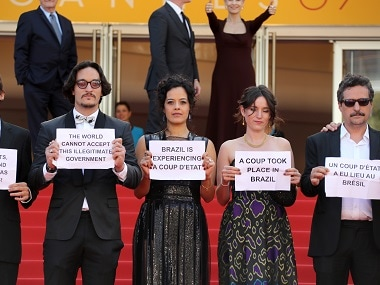 """(From left) Allan Souza, Maeve Jinkings, Emilie Lesclaux and Kleber Mendonca Filho hold protest signs as they arrive on Tuesday for the screening of the film """"Aquarius"""" at the 69th Cannes Film Festival in Cannes. AFP"""