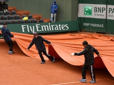 Ground staff pull on the covers as rain wrecked havoc on day one of the 2016 French Open. Getty Images