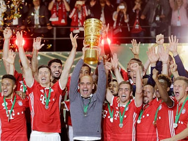 Bayern head coach Pep Guardiola holds up the German Cup trophy. AP