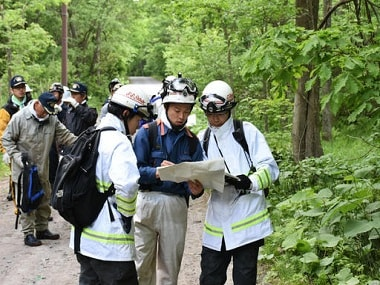 Rescuers search for the boy in a forest in Nanae town. AP.