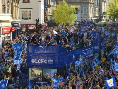 Leicester City's Claudio Ranieri stands with the Premier league trophy as the team take part in an open-top bus parade. AFP