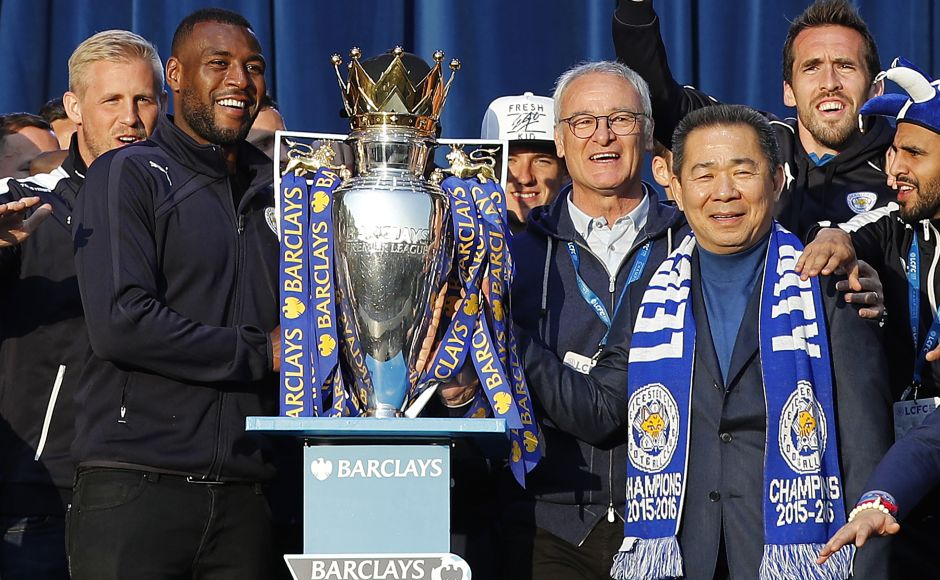 Leicester City's Thai owner Vichai Srivaddhanaprabha, Claudio Ranieri and Wes Morgan stand with the trophy on stage Victoria Park after the open-bus parade. AFP / ADRIAN DENNIS