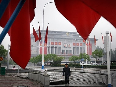 A North Korean man walks out of an underpass while seen framed by the Workers' Party flags, in front of the April 25 House of Culture, the venue for the 7th Congress of the Workers' Party of Korea on Friday. AP