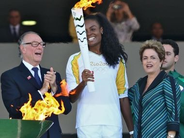 Brazilian volleyball player Fabiana Claudino holds the Olympic torch along with Brazilian President Dilma Rousseff. AFP
