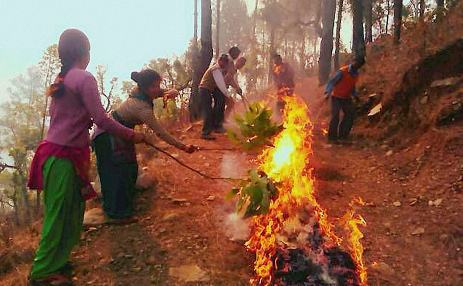 Local people extinguishing the fire in the forests at Kotdwar, Uttarakhand. PTI
