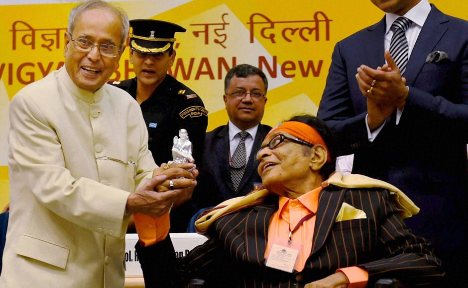 President Pranab Mukherjee shows a silver statue of Sai Baba gifted to him by veteran actor Manoj Kumar. PTI image.