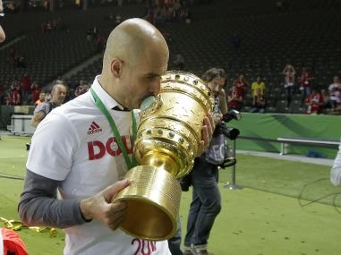 Bayern Munich head coach Pep Guardiola kisses the trophy after winning the German Cup. AP