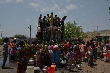 Women, one with infant in arms, gather to collet water from the twice-a-week government tanker while agile children climb atop the tanker to affix pipes in drought hit village Wasangaon, District Latur. Jayati Saha.