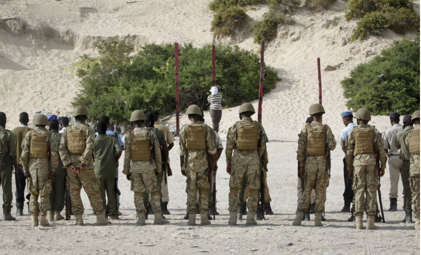 Hassan Hanafi Haji, center, a former journalist accused of belonging to al-Shabab and involvement in the killings of five Somali journalists, is tied to a wooden post as he is prepared to be executed by firing squad, at a police academy in Somalia on 11 April. AP